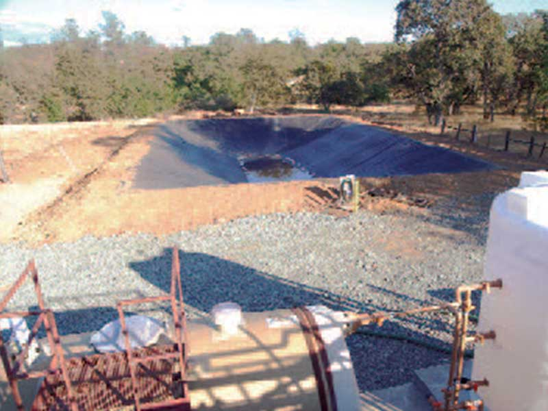 Wide view of an excavated pond for treating wastewater