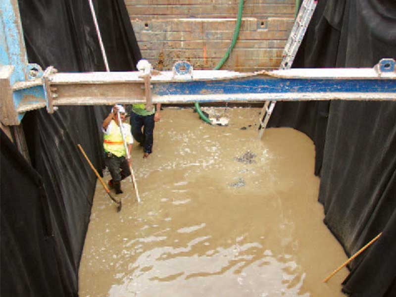 Workers installing a wastewater system in an excavation pit